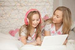 Η μητέρα και η κόρη βάζουν στο κρεβάτι στις πυτζάμες και έχουν τη διασκέδαση, χρησιμοποιούν το lap-top και ακούνε μουσική από τα  Στοκ εικόνες με δικαίωμα ελεύθερης χρήσης
