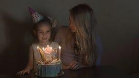 Η μητέρα και η κόρη εκρήγνυνται τα κεριά σε ένα κέικ και την παραγωγή γενεθλίων μιας επιθυμίας τα γενέθλια ενός μικρού κοριτσιού Στοκ φωτογραφία με δικαίωμα ελεύθερης χρήσης