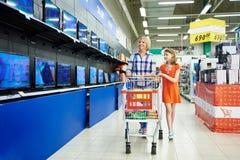 Η μητέρα και η κόρη εξετάζουν τις TV LCD στο κατάστημα στοκ εικόνα