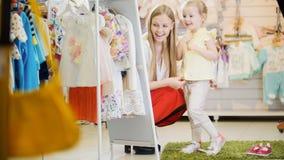Η μητέρα και η κόρη προσπαθούν στο κοστούμι στο κατάστημα ιματισμού παιδιών ` s Στοκ Φωτογραφία