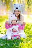 Η μητέρα και η κόρη στα πλεκτά καπέλα αντέχουν, με μια κούκλα Στοκ εικόνα με δικαίωμα ελεύθερης χρήσης