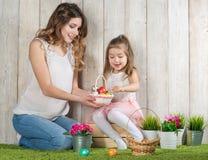 Η μητέρα και η κόρη συλλέγουν τα αυγά Πάσχας στοκ φωτογραφία