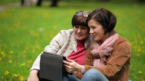 Η μητέρα και η κόρη χρησιμοποιούν την κινητή συσκευή μαζί υπαίθρια Η νέα γυναίκα παρουσιάζει κάτι στο mom της στην ταμπλέτα απόθεμα βίντεο