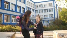 Η μητέρα και η κόρη ένα πρώτος-γκρέιντερ που κρατά μαζί τα χέρια είναι εξωσχολικές μετά από το σχολείο απόθεμα βίντεο