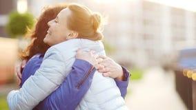 Η μητέρα και η κόρη αγκαλιάζουν στην οδό Είναι ντυμένα την άνοιξη σακάκια Ηλιοβασίλεμα το λουλούδι ημέρας δίνει το γιο μητέρων mu απόθεμα βίντεο