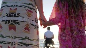 Η μητέρα και η κόρη κρατούν τα χέρια στη συνεδρίαση πατέρων υποβάθρου στην αναπηρική καρέκλα απόθεμα βίντεο