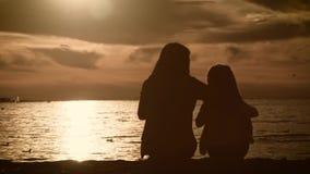 Η μητέρα και η κόρη σκιαγραφιών κάθονται στην παραλία στο ηλιοβασίλεμα Έννοια της φιλικής οικογένειας, τρόπος ζωής απόθεμα βίντεο