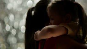 Η μητέρα και η κόρη της αγκαλιάζουν Η βροχή είναι στο υπόβαθρο Έχουν πολλή διασκέδαση επειδή σήμερα είναι ημέρα μητέρων ` s φιλμ μικρού μήκους