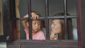 Η μητέρα και λίγη κόρη φαίνονται έξω το παράθυρο με τις τρυπώντας συγκινήσεις απόθεμα βίντεο
