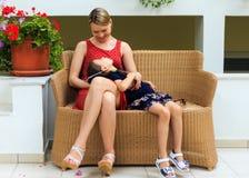Η μητέρα και η νέα κόρη κάθονται σε μια καρέκλα ινδικού καλάμου ενός μεσογειακού ξενοδοχείου στοκ εικόνες με δικαίωμα ελεύθερης χρήσης
