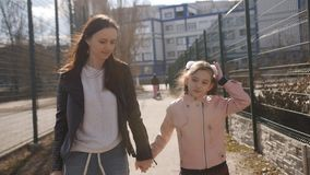 Η μητέρα και η νέα κόρη πηγαίνουν από το σχολείο από κοινού Η μητέρα φέρνει το σακίδιο πλάτης ενός μικρού μαθητή φιλμ μικρού μήκους