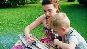 Η μητέρα και ο γιος διαβάζουν ένα βιβλίο σε ένα πάρκο στη χλόη φιλμ μικρού μήκους