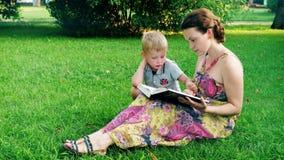 Η μητέρα και ο γιος διαβάζουν ένα βιβλίο σε ένα πάρκο στη χλόη απόθεμα βίντεο