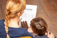 Η μητέρα και ο γιος είναι ευχαριστημένοι από το καλό σχολικό πιστοποιητικό - μετάφραση: ημέρα πιστοποιητικών της μουσικής πειθαρχ στοκ εικόνα με δικαίωμα ελεύθερης χρήσης
