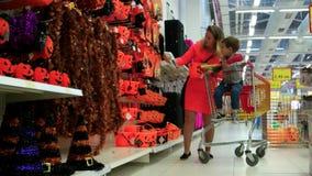Η μητέρα και ο γιος επιλέγουν τα προϊόντα για αποκριές, οικογένεια προετοιμαμένος για την παραμονή όλου του Hallows, εορτασμός απ φιλμ μικρού μήκους