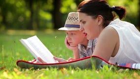 Η μητέρα και ο γιος ξοδεύουν τη χρονική ανάγνωσή τους σε ένα θερινό απόγευμα στο πάρκο απόθεμα βίντεο