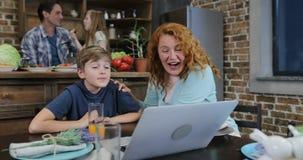 Η μητέρα και ο γιος που μιλούν κάνουν την τηλεοπτική κλήση χρησιμοποιώντας τα μαγειρεύοντας τρόφιμα πατέρων και κορών lap-top στη απόθεμα βίντεο