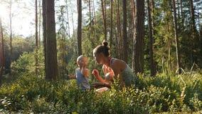 Η μητέρα και ο γιος στην ηλικία ενός έτους συλλέγουν και τρώνε τα άγρια βακκίνια στο δάσος φιλμ μικρού μήκους