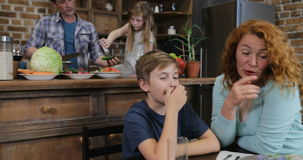 Η μητέρα και ο γιος χρησιμοποιούν την ψηφιακή ταμπλέτα ενώ πατέρας με την κόρη που αλατίζει τα λαχανικά για τη σαλάτα γευμάτων στ απόθεμα βίντεο