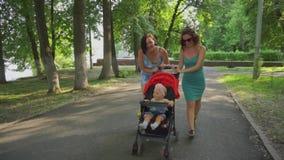 Η μητέρα και ο φίλος της περπατούν με ένα μικρό παιδί που κάθεται σε έναν περιπατητή απόθεμα βίντεο