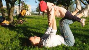 Η μητέρα και το μωρό βρίσκονται στη χλόη, mom παίζει με το μωρό της στο πάρκο στο ηλιοβασίλεμα Στοκ Φωτογραφία