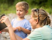 Η μητέρα και το μωρό εξετάζουν το τηλέφωνο κυττάρων στοκ φωτογραφία με δικαίωμα ελεύθερης χρήσης