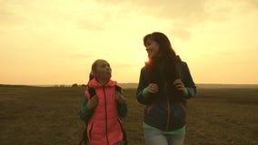 Η μητέρα και το παιδί τουριστών πηγαίνουν στο ηλιοβασίλεμα στα βουνά ευτυχής οικογένεια στα ταξίδια διακοπών έννοια της αθλητικής απόθεμα βίντεο
