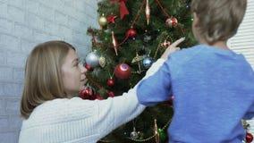 Η μητέρα και το παιδί διακοσμούν το χριστουγεννιάτικο δέντρο μαζί στην ημέρα απόθεμα βίντεο