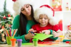 Η μητέρα και το παιδί κόβουν να προετοιμαστούν στα Χριστούγεννα Στοκ Εικόνα