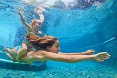 Η μητέρα, κοριτσάκι κολυμπά και βουτά υποβρύχιος στη λίμνη στοκ εικόνα