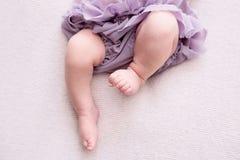 Η μητέρα κρατά τα πόδια του νεογέννητου μωρού με τα χέρια της, δάχτυλα στα αγκαλιάσματα ποδιών, μητρικής φροντίδας, αγάπης και οι στοκ εικόνα με δικαίωμα ελεύθερης χρήσης