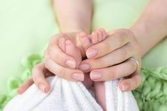 Η μητέρα κρατά τα πόδια του νεογέννητου μωρού με τα χέρια της, δάχτυλα στα αγκαλιάσματα ποδιών, μητρικής φροντίδας, αγάπης και οι στοκ εικόνες