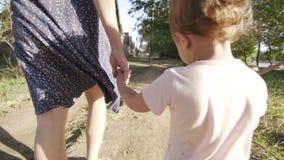 Η μητέρα κρατά το χέρι της μικρής κόρης παιδιών ` s περπατώντας απόθεμα βίντεο
