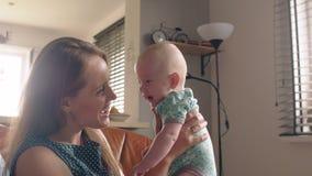 Η μητέρα κρατά ψηλά τη λατρευτή συνεδρίαση μωρών χαμόγελού της στον καναπέ 4K στοκ φωτογραφία με δικαίωμα ελεύθερης χρήσης