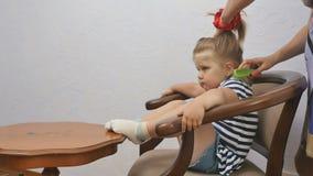 Η μητέρα κτενίζει μια τρίχα κορών ` s και κάνει ένα ponytail για το μικρό κορίτσι απόθεμα βίντεο
