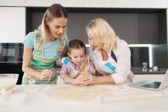 Η μητέρα, η κόρη και η γιαγιά της κάνουν τα σπιτικά μπισκότα Διαμορφώνουν ένα μπισκότο με ένα ποτήρι Στοκ Εικόνα