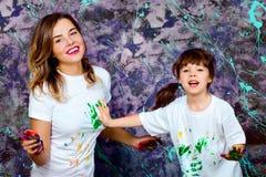 Η μητέρα μαζί με μια κόρη παρουσιάζεται με τους φοίνικες που λερώνονται με Στοκ Εικόνες
