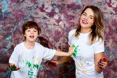Η μητέρα μαζί με μια κόρη παρουσιάζεται με τους φοίνικες που λερώνονται με Στοκ Εικόνα