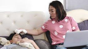 Η μητέρα με ένα παιδί προσπαθεί να εργαστεί στο φορητό προσωπικό υπολογιστή στο σπίτι, το άρρωστο αγόρι Α βρισκόταν στο κρεβάτι φιλμ μικρού μήκους