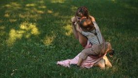 Η μητέρα με ένα παιδί φαίνεται παιχνίδι στη χλόη φιλμ μικρού μήκους