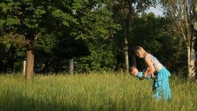 Η μητέρα με ένα παιδί φαίνεται παιχνίδι στη χλόη απόθεμα βίντεο