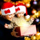 Η μητέρα με λίγο παιδί ανοίγει το κιβώτιο με τα δώρα στα Χριστούγεννα Στοκ Εικόνες