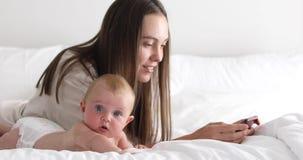 Η μητέρα με λίγη κόρη χρησιμοποιεί το smartphone απόθεμα βίντεο