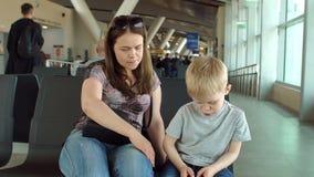 Η μητέρα με μια συνεδρίαση παιδιών στο σαλόνι αναχώρησης, αγόρι παίζεται στο τηλέφωνο φιλμ μικρού μήκους