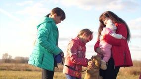 Η μητέρα με τα παιδιά και το σκυλί περπατούν στο πάρκο φθινοπώρου, οικογενειακοί περίπατοι με ένα κατοικίδιο ζώο απόθεμα βίντεο