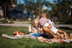 Η μητέρα με τα παιδιά έχει τη διασκέδαση στη χλόη Στοκ εικόνες με δικαίωμα ελεύθερης χρήσης