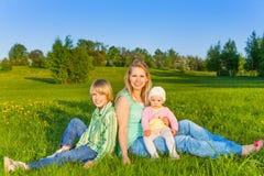 Η μητέρα με τα παιδιά κάθεται στη χλόη στο πάρκο Στοκ φωτογραφίες με δικαίωμα ελεύθερης χρήσης