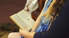 Η μητέρα με την αγαπημένη μικρή κόρη κάθεται σε μια καρέκλα και διαβάζει τα παραμύθια φιλμ μικρού μήκους