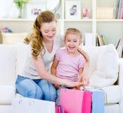 Η μητέρα με την κόρη με τις αγορές τοποθετεί σε σάκκο στο σπίτι Στοκ Εικόνες