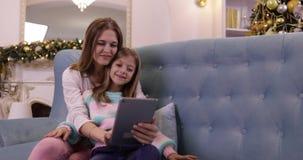 Η μητέρα με την κόρη στον καναπέ που χρησιμοποιεί την ευτυχή χαμογελώντας νέα οικογένεια υπολογιστών ταμπλετών διακόσμησε πλησίον απόθεμα βίντεο